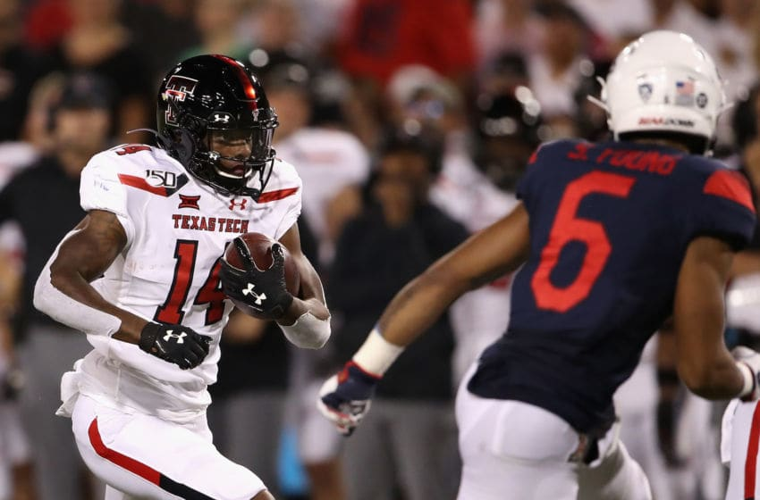 TUCSON, ARIZONA - SEPTEMBER 14: Wide receiver Xavier White #14 of the Texas Tech Red Raiders runs with the football after a reception against safety Scottie Young Jr. #6 of the Arizona Wildcats during the first half of the NCAAF game at Arizona Stadium on September 14, 2019 in Tucson, Arizona. (Photo by Christian Petersen/Getty Images)