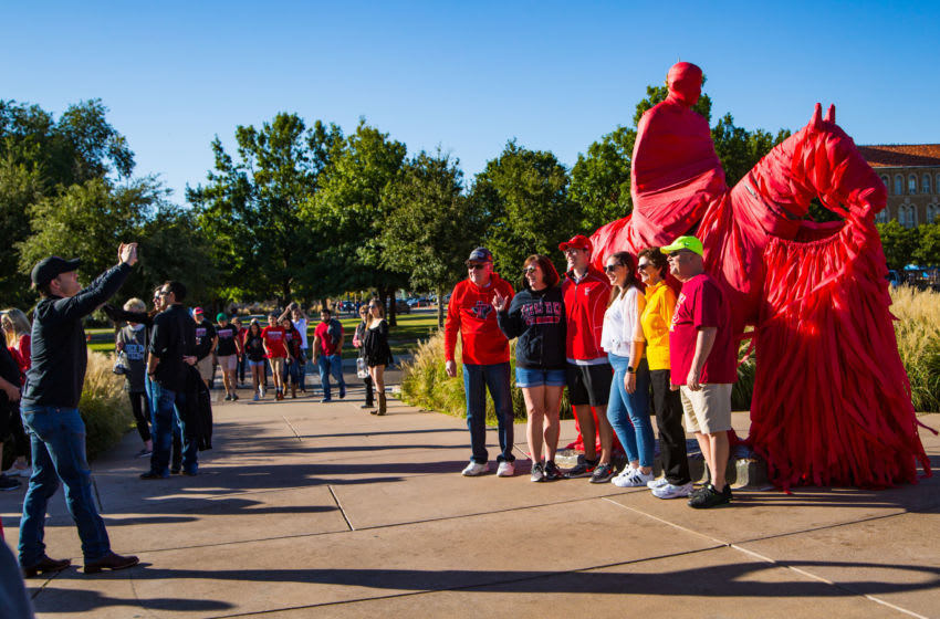 LUBBOCK, TEXAS - OCTOBER 19: Fans pose for a photo with the Will Rogers and Soapsuds statue before the college football game between the Texas Tech Red Raiders and the Iowa State Cyclones on October 19, 2019 at Jones AT&T Stadium in Lubbock, Texas. (Photo by John E. Moore III/Getty Images)