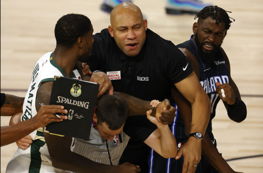 LAKE BUENA VISTA, FLORIDA - AUGUST 22: Referee Kevin Scott #24 and Milwaukee Bucks assistant coach Darvin Ham break up a fight between Marvin Williams #20 of the Milwaukee Bucks grabs and James Ennis III #11 of the Orlando Magic in Game Three of the Eastern Conference First Round during the 2020 NBA Playoffs at The Field House at ESPN Wide World Of Sports Complex on August 22, 2020 in Lake Buena Vista, Florida. Both players were ejected from the game. NOTE TO USER: User expressly acknowledges and agrees that, by downloading and or using this photograph, User is consenting to the terms and conditions of the Getty Images License Agreement. (Photo by Mike Ehrmann/Getty Images)