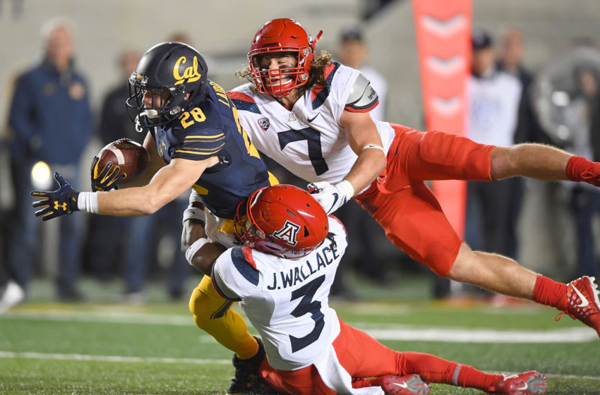 BERKELEY, CA - OCTOBER 21: Patrick Laird #28 of the California Golden Bears draggs Colin Schooler #7 and Jarrius Wallace #3 of the Arizona Wildcats into the endzone scoring on an 18-yard touchdown run during their NCAA football game at California Memorial Stadium on October 21, 2017 in Berkeley, California. (Photo by Thearon W. Henderson/Getty Images)