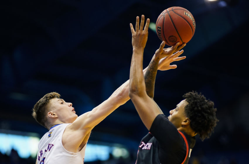 Feb 20, 2021; Lawrence, Kansas, USA; Kansas Jayhawks guard Christian Braun (2) blocks a shot by Texas Tech Red Raiders guard Kyler Edwards (11) during the second half at Allen Fieldhouse. Mandatory Credit: Jay Biggerstaff-USA TODAY Sports