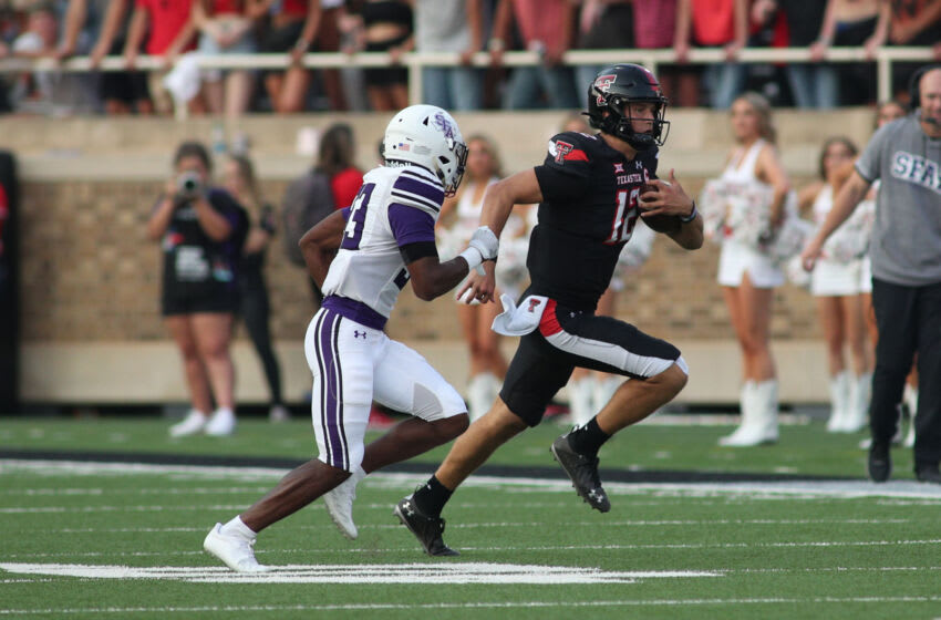 Sep 11, 2021; Lubbock, Texas, USA; Texas Tech Red Raiders quarterback Tyler Slough (12) rushes around the end against Stephen F. Austin Lumberjacks safety Zac Gulley (33) in the first half at Jones AT&T Stadium. Mandatory Credit: Michael C. Johnson-USA TODAY Sports