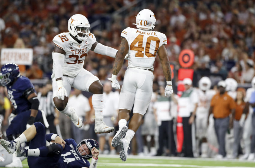 HOUSTON, TX - SEPTEMBER 14: Ayodele Adeoye #40 of the Texas Longhorns and Malcolm Roach #32 celebrate after sacking Tom Stewart #14 of the Rice Owls in the second half at NRG Stadium on September 14, 2019 in Houston, Texas. (Photo by Tim Warner/Getty Images)
