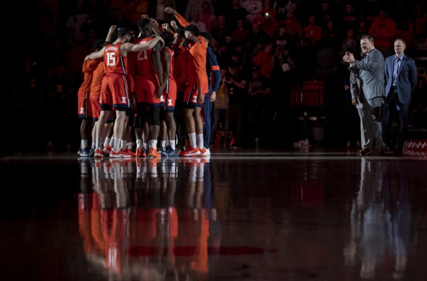 CHAMPAIGN, IL - DECEMBER 11: Members of the Illinois Fighting Illini huddle as Head coach Brad Underwood of the Illinois Fighting Illini watches before the game against the Michigan Wolverines at State Farm Center on December 11, 2019 in Champaign, Illinois. (Photo by Michael Hickey/Getty Images)