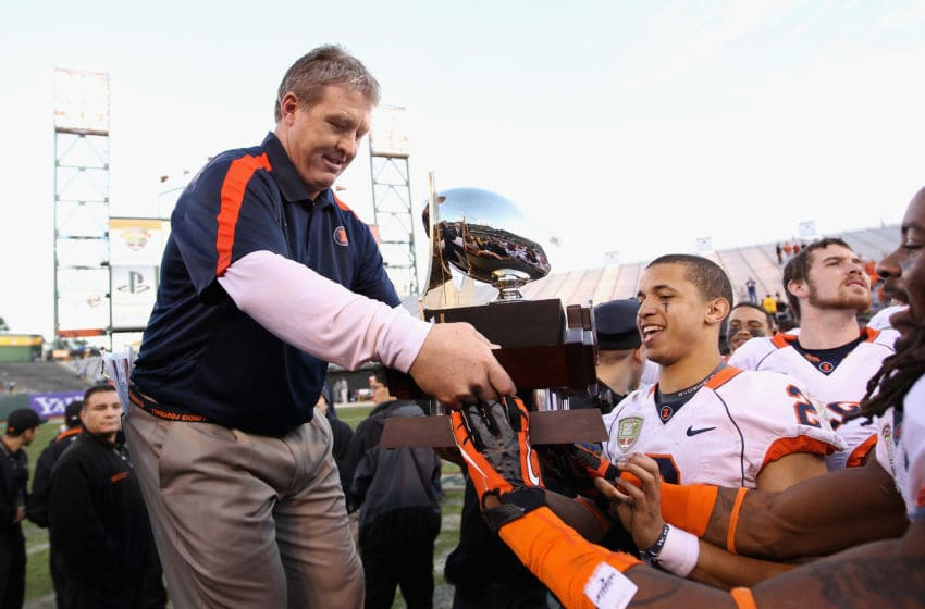 SAN FRANCISCO, CA - DECEMBER 31: Interim head coach Vic Koenning of the Illinois Fighting Illini hands the trophy to Nathan Scheelhaase #2 after they beat the UCLA Bruins in the Kraft Fight Hunger Bowl at AT&T Park on December 31, 2011 in San Francisco, California. (Photo by Ezra Shaw/Getty Images)