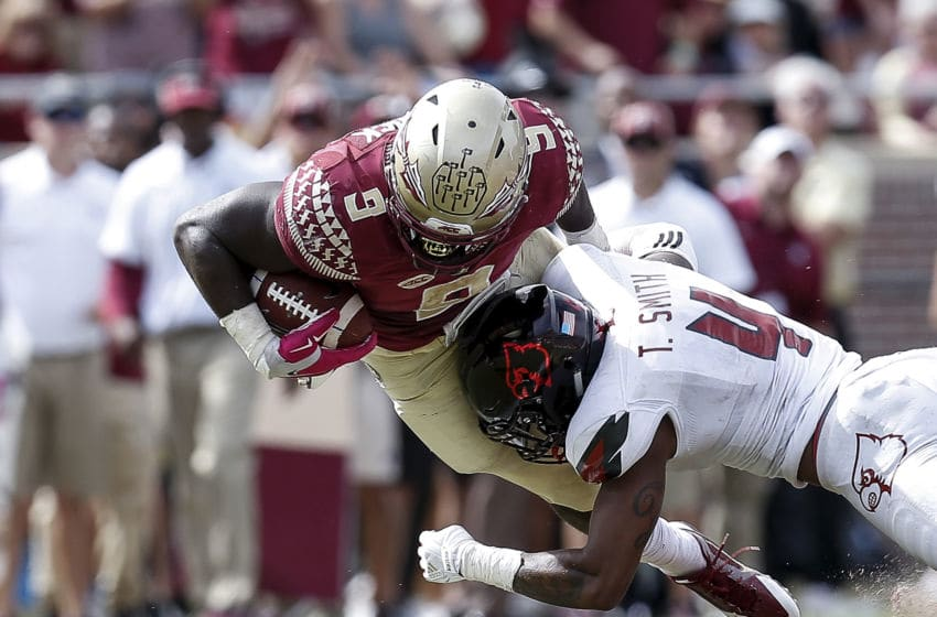 TALLAHASSEE, FL - OCTOBER 21: Runningback Jacques Patrick #9 of the Florida State Seminoles is tackled by Safety TreSean Smith #4 of the Louisville Cardinals during the game at Doak Campbell Stadium on Bobby Bowden Field on October 21, 2017 in Tallahassee, Florida. Louisville defeated Florida State 31 to 28. (Photo by Don Juan Moore/Getty Images)