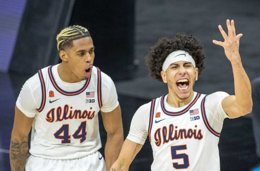 Illinois Fighting Illini guard Andre Curbelo (5) gets fans pumped up as teammate Adam Miller (44) cheers Curbelo's shot against Iowa Hawkeyes on Saturday, March 13, 2021, during the men's Big Ten basketball tournament from Lucas Oil Stadium. Iowa Vs Illinois