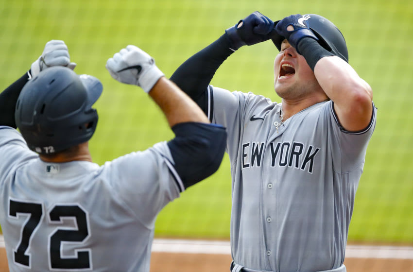 Luke Voit #59 of the New York Yankees reacts after hitting a home run with Mike Ford in the sixth inning of game one of the MLB doubleheader against the Atlanta Braves at Truist Park on August 26, 2020 in Atlanta, Georgia. (Photo by Todd Kirkland/Getty Images)