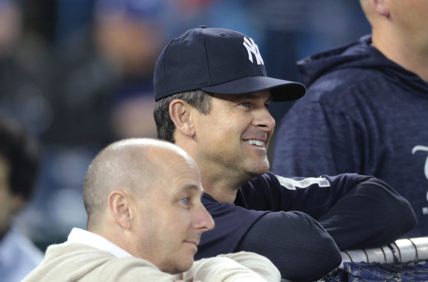 TORONTO, ON - MARCH 30: Manager Aaron Boone #17 of the New York Yankees and general manager Brian Cashman look on during batting practice before the start of MLB game action against the Toronto Blue Jays at Rogers Centre on March 30, 2018 in Toronto, Canada. (Photo by Tom Szczerbowski/Getty Images) *** Local Caption *** Aaron Boone;Brian Cashman