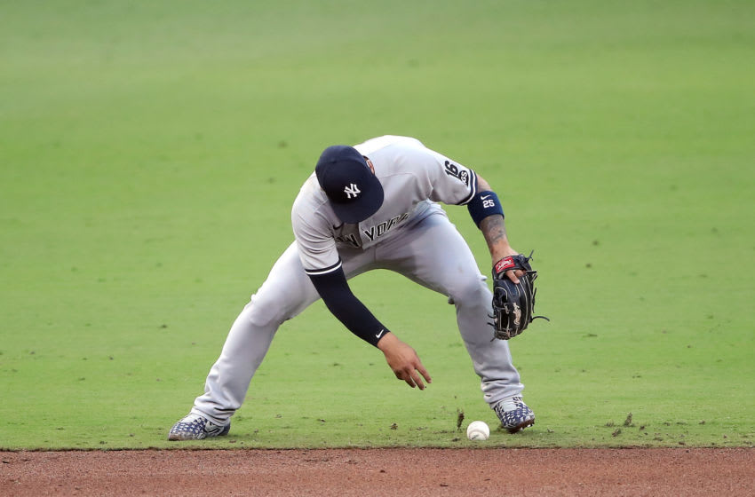 SAN DIEGO, CALIFORNIA - OCTOBER 09: Gleyber Torres #25 of the New York Yankees commits a fielding error on a ground ball hit by Yandy Diaz (not pictured) of the Tampa Bay Rays during the fourth inning in Game Five of the American League Division Series at PETCO Park on October 09, 2020 in San Diego, California. (Photo by Sean M. Haffey/Getty Images)