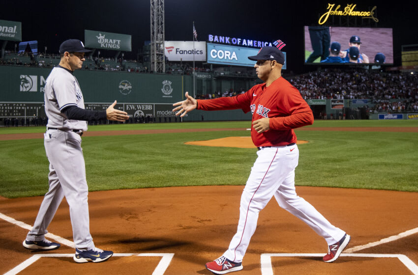 BOSTON, MA - OCTOBER 05: Manager Aaron Boone of the New York Yankees shakes hands with Manager Alex Cora of the Boston Red Sox as starting lineups are introduced during a pre-game ceremony before the 2021 American League Wild Card game at Fenway Park on October 5, 2021 in Boston, Massachusetts. (Photo by Billie Weiss/Boston Red Sox/Getty Images)