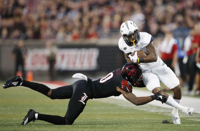 LOUISVILLE, KY - OCTOBER 05: Rodjay Burns #10 of the Louisville Cardinals makes a tackle near the sideline against Clinton Lynch #22 of the Georgia Tech Yellow Jackets in the first half of the game at Cardinal Stadium on October 5, 2018 in Louisville, Kentucky. (Photo by Joe Robbins/Getty Images)