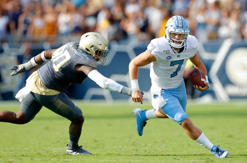 ATLANTA, GEORGIA - OCTOBER 05: Sam Howell #7 of the North Carolina Tar Heels rushes out of the pocket away from Kelton Dawson #90 of the Georgia Tech Yellow Jackets at Bobby Dodd Stadium on October 05, 2019 in Atlanta, Georgia. (Photo by Kevin C. Cox/Getty Images)