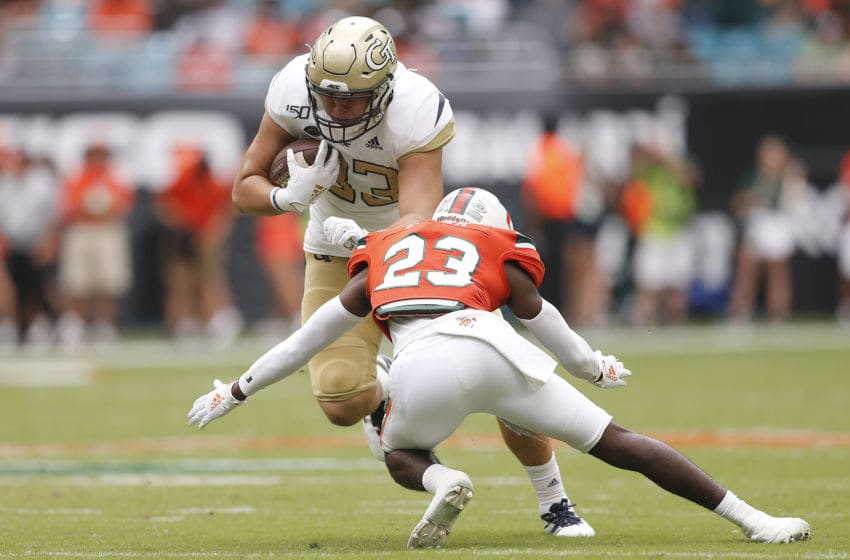 MIAMI, FLORIDA - OCTOBER 19: Dylan Deveney #83 of the Georgia Tech Yellow Jackets is tackled by Te'Cory Couch #23 of the Miami Hurricanes during the second half at Hard Rock Stadium on October 19, 2019 in Miami, Florida. (Photo by Michael Reaves/Getty Images)