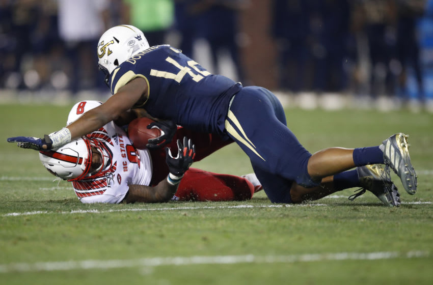 ATLANTA, GA - NOVEMBER 21: Ricky Person Jr. #8 of the North Carolina State Wolfpack is tackled by Jordan Domineck #42 of the Georgia Tech Yellow Jackets during the first half at Bobby Dodd Stadium on November 21, 2019 in Atlanta, Georgia. (Photo by Todd Kirkland/Getty Images)