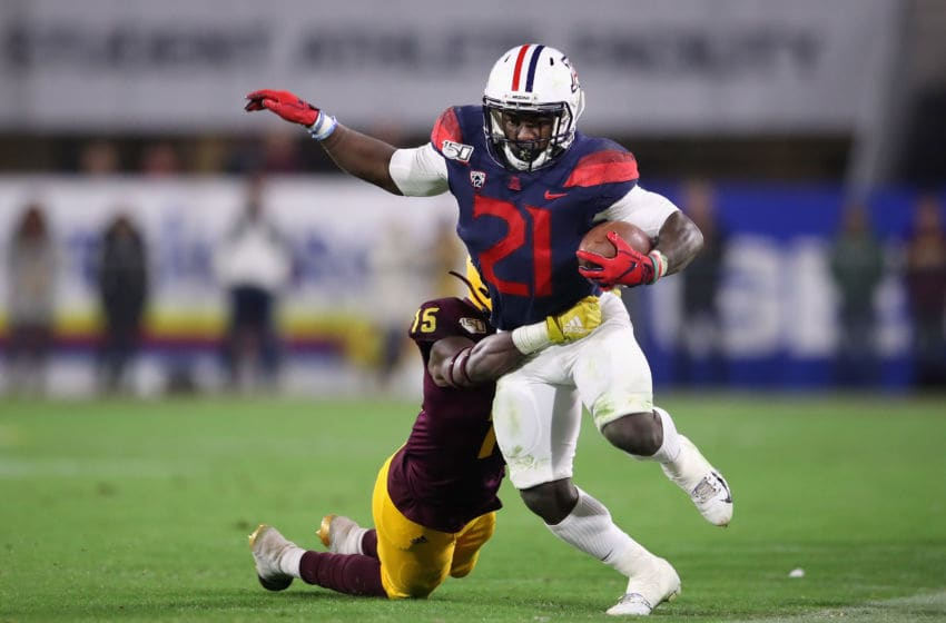 TEMPE, ARIZONA - NOVEMBER 30: Running back J.J. Taylor #21 of the Arizona Wildcats rushes the football against safety Cam Phillips #15 of the Arizona State Sun Devils during the first half of the NCAAF game at Sun Devil Stadium on November 30, 2019 in Tempe, Arizona. (Photo by Christian Petersen/Getty Images)