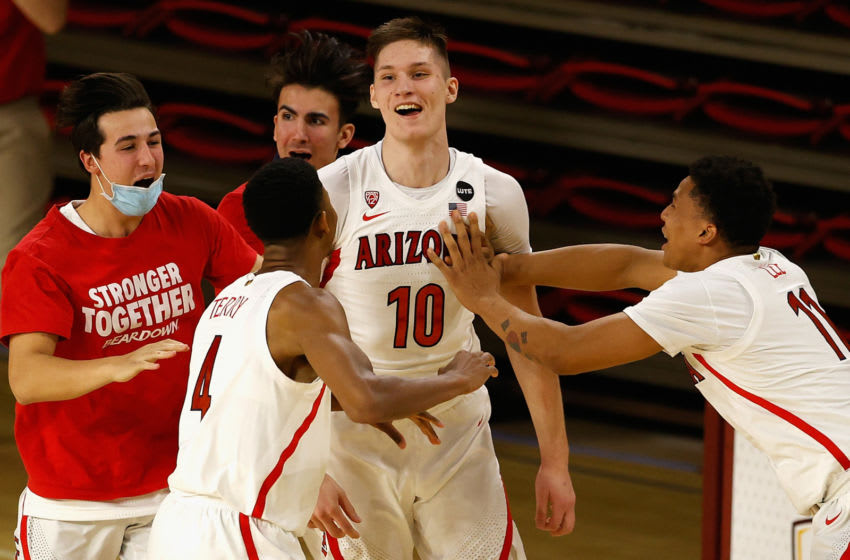TEMPE, ARIZONA - JANUARY 21: Azuolas Tubelis #10 of the Arizona Wildcats celebrates with teammates Dalen Terry #4 and Ira Lee #11 after scoring against the Arizona State Sun Devils during the final seconds to win the NCAAB game at Desert Financial Arena on January 21, 2021 in Tempe, Arizona. The Wildcats defeated the Sun Devils 84-82. (Photo by Christian Petersen/Getty Images)