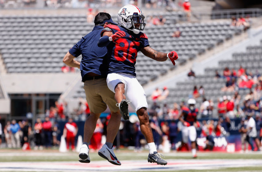 TUCSON, ARIZONA - APRIL 24: Wide receiver Stanley Berryhill III #86 of the Arizona Wildcats (Team Blue) celebrates after a reception with former NFL athlete and University of Arizona Alum, Tedy Bruschi during the Arizona Spring game at Arizona Stadium on April 24, 2021 in Tucson, Arizona. (Photo by Christian Petersen/Getty Images)
