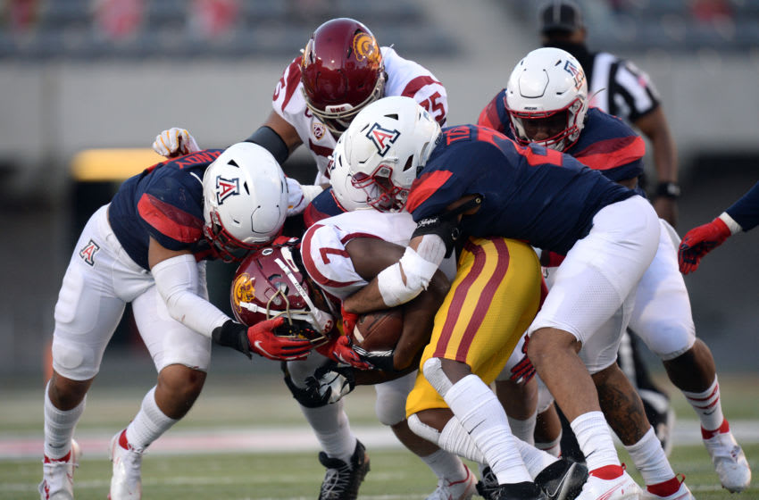 Nov 14, 2020; Tucson, Arizona, USA; USC Trojans running back Stephen Carr (7) is stopped by Arizona Wildcats defenders during the second half at Arizona Stadium. Mandatory Credit: Joe Camporeale-USA TODAY Sports