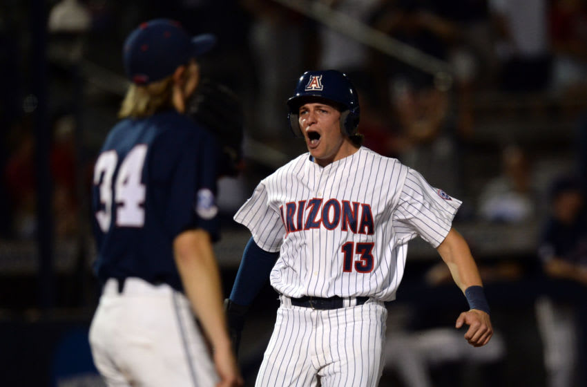 Jun 11, 2021; Tucson, Arizona, USA; Arizona Wildcats outfielder Tyler Casagrande (13) reacts as he scores a run in front of Ole Miss Rebels pitcher Tyler Myers (34) during the eighth inning during the NCAA Baseball Tucson Super Regional at Hi Corbett Field. Mandatory Credit: Joe Camporeale-USA TODAY Sports
