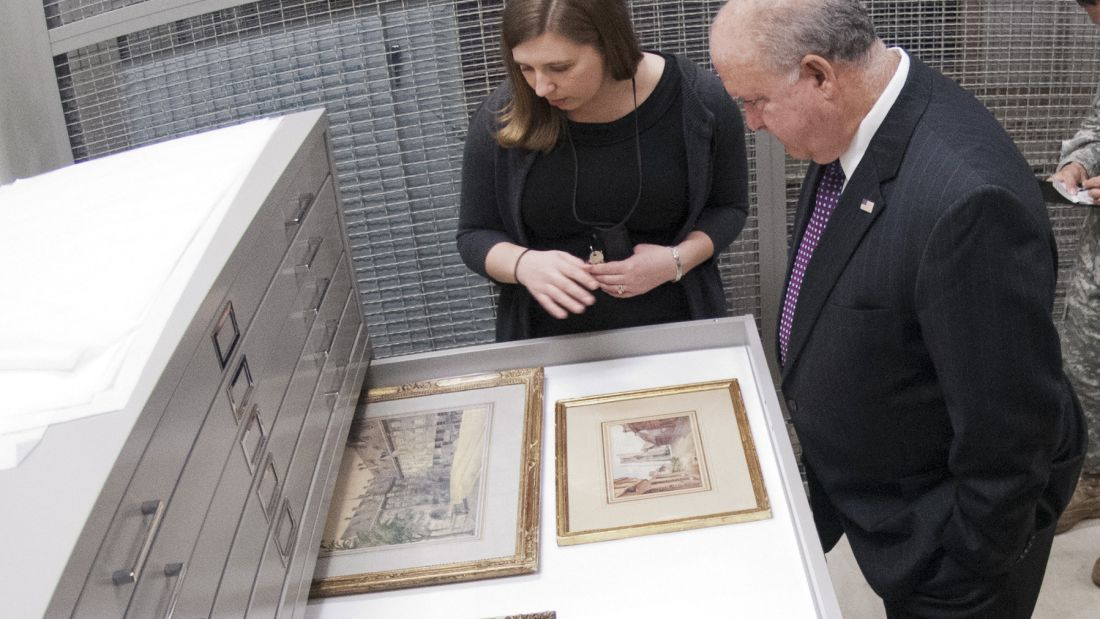Art Curator Sarah Forgey shows Under Secretary of the Army Joseph W. Westphal four watercolors by Adolf Hitler at Fort Belvoir, Virginia.
