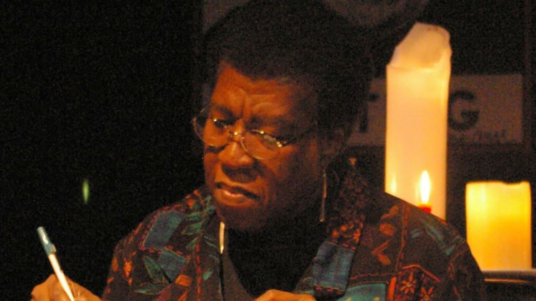 Octavia E. Butler autographs a copy of Fledgling at a book signing.