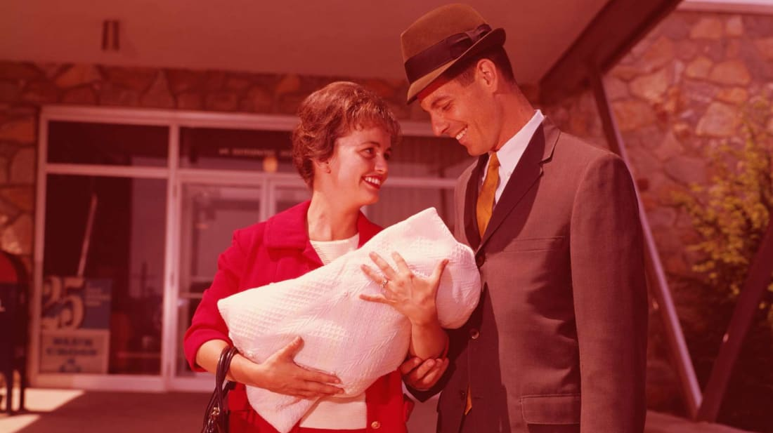 A happy couple leaves the hospital with their newborn baby in the 1960s.