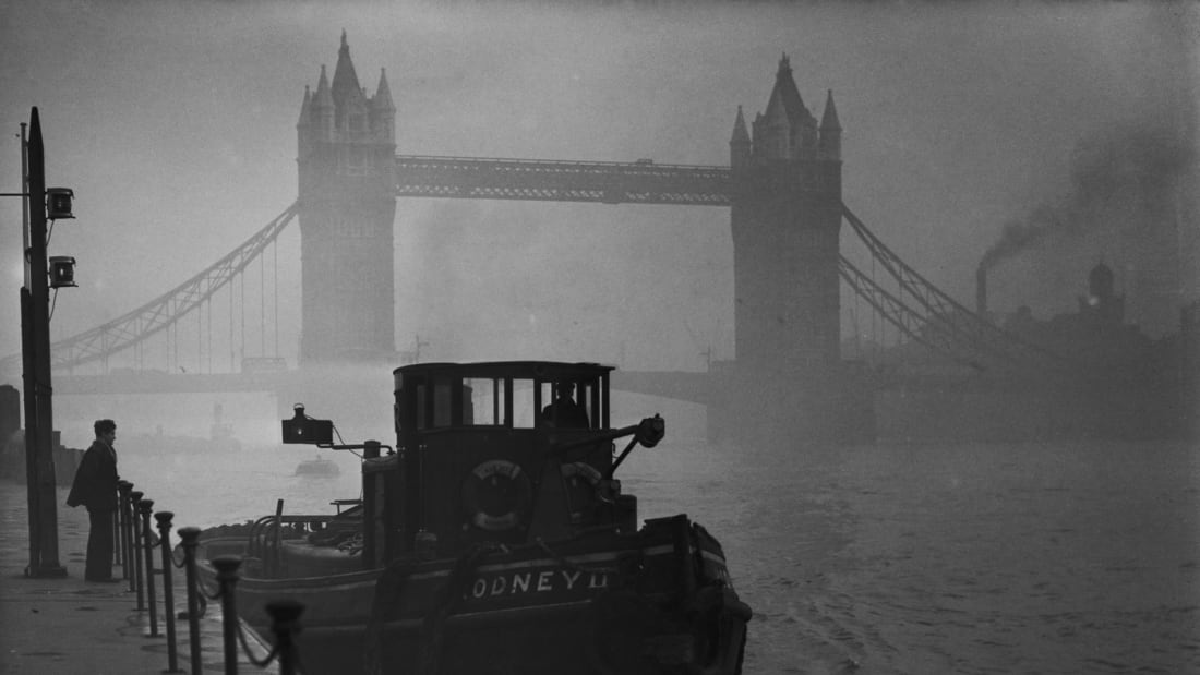 A tugboat on the Thames near Tower Bridge in heavy smog, 1952.
