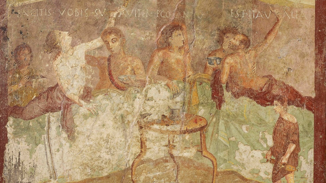 A fresco wall panel showing a dinner party with painted message