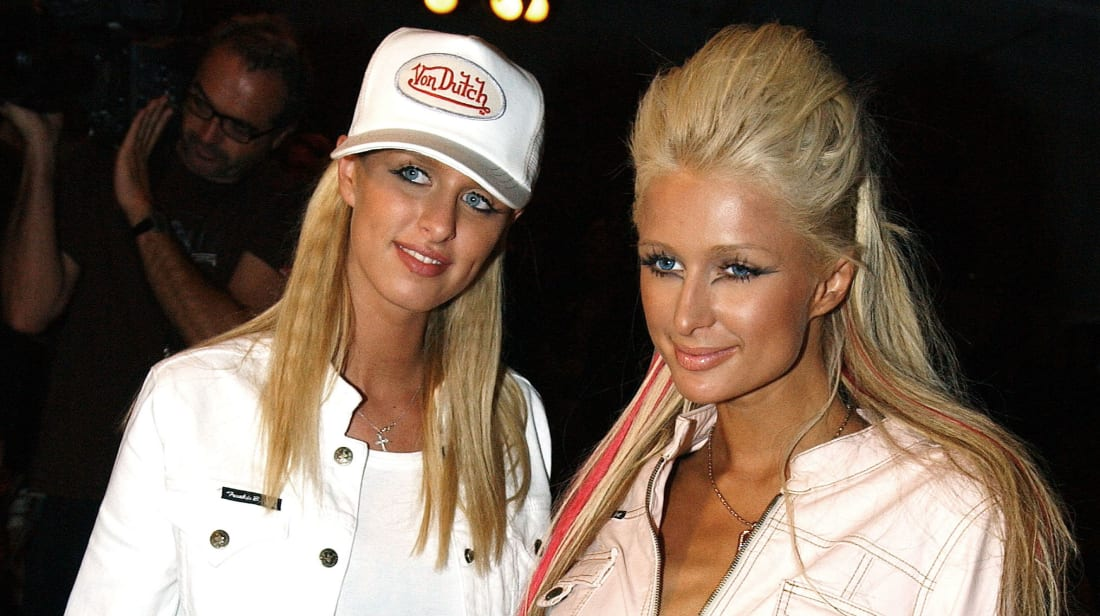 Nicky and Paris Hilton pose at the Frankie B Fall 2003 preview during the Mercedes-Benz Shows LA Fashion Week. Back when trucker hats were a thing.