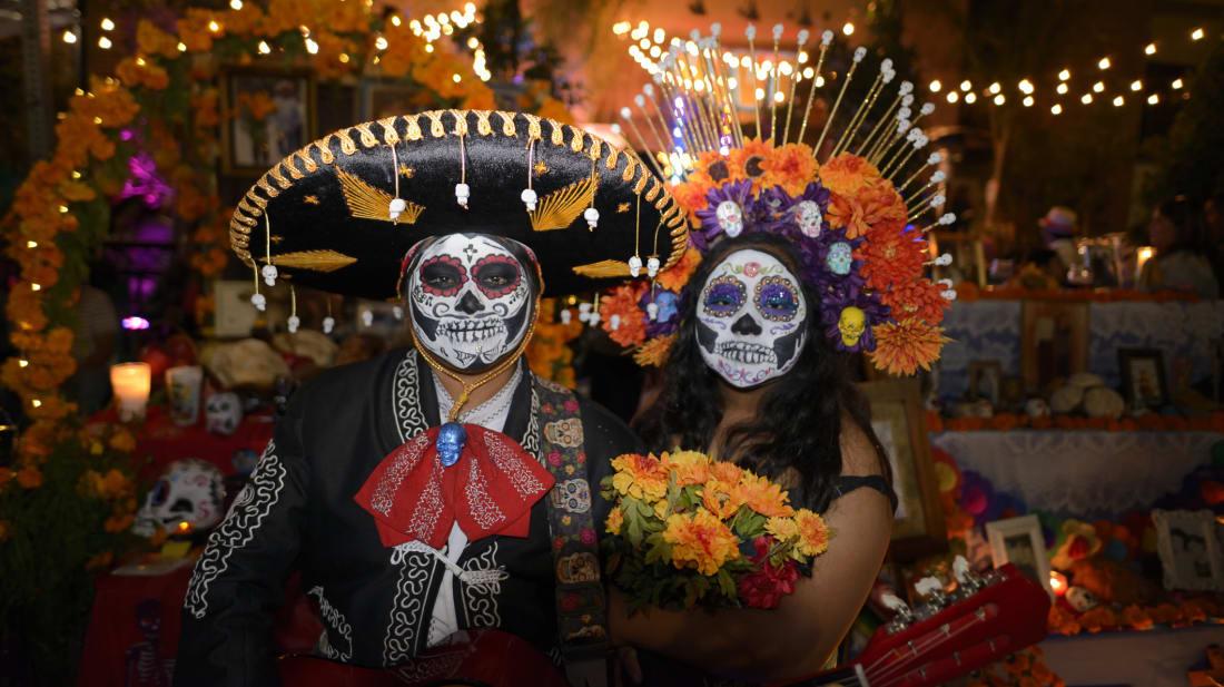 Participants standing in front of an altar during Día de los Muertos