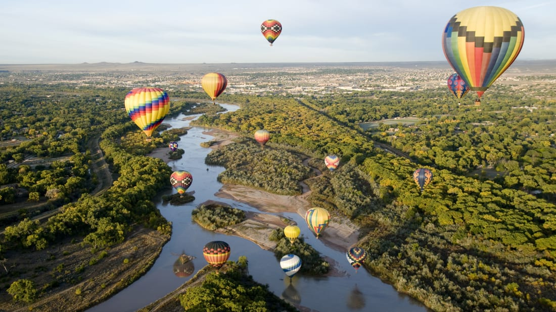 Hot air balloons drifting over the Rio Grande River in Albuquerque, New Mexico.