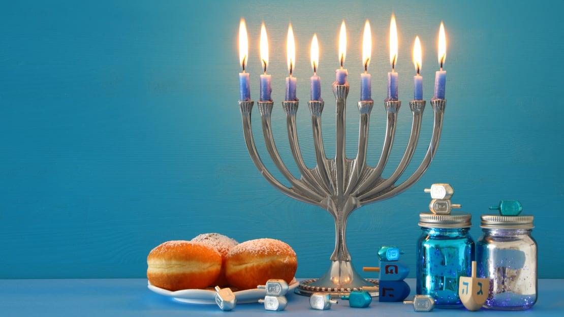A Hanukkah menorah (traditional candelabra), dreidels (spinning tops), and sufganiyot (jelly donuts)