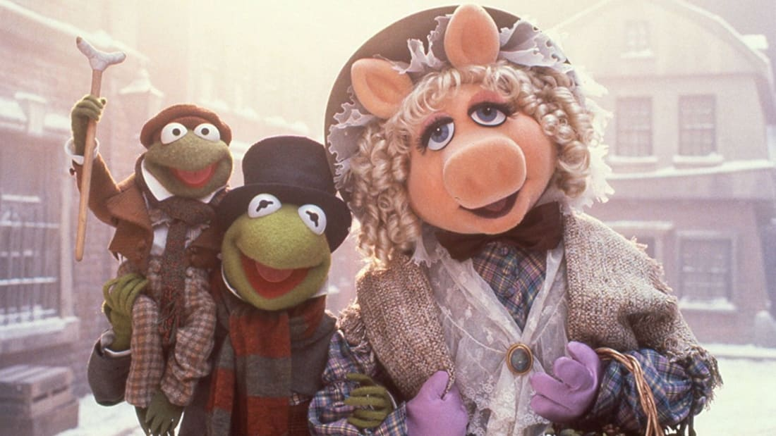 Kermit and Miss Piggy with Tiny Tim in The Muppet Christmas Carol (1992).