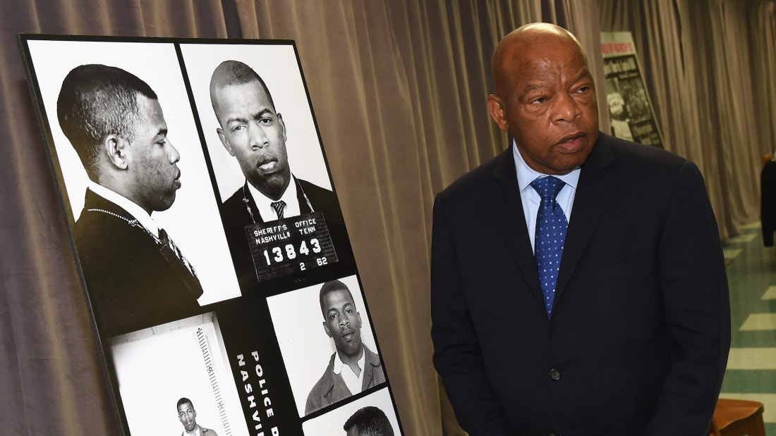 John Lewis poses with images from his first arrests for leading a nonviolent sit-in at Nashville's segregated lunch counters.