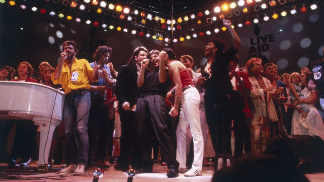George Michael, Bob Geldof, Bono, Paul McCartney, Freddie Mercury, David Bowie, and Howard Jones gather together for the Live Aid finale at London's Wembley Stadium.