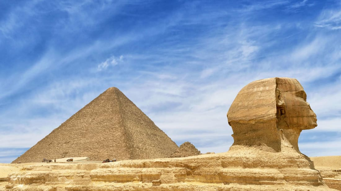 The Great Sphinx with the Pyramids of Giza in the distance.