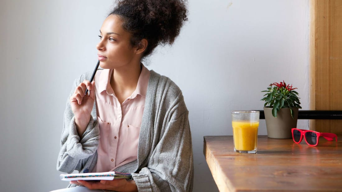 This woman systematically drinks orange juice while her creative juices are flowing.