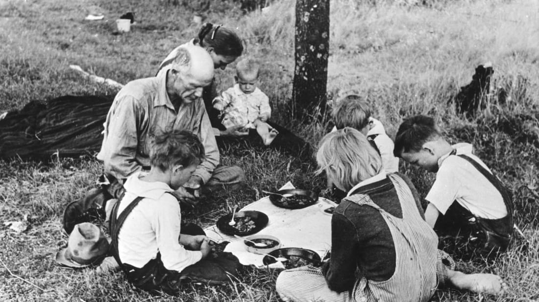 A family eating dinner by the roadside circa 1930.