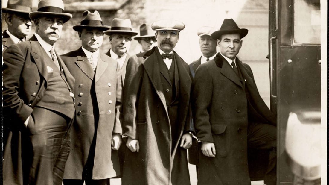 Nicola Sacco (right) and Bartolomeo Vanzetti (third from right, with mustache) head back to jail accompanied by deputy sheriffs.