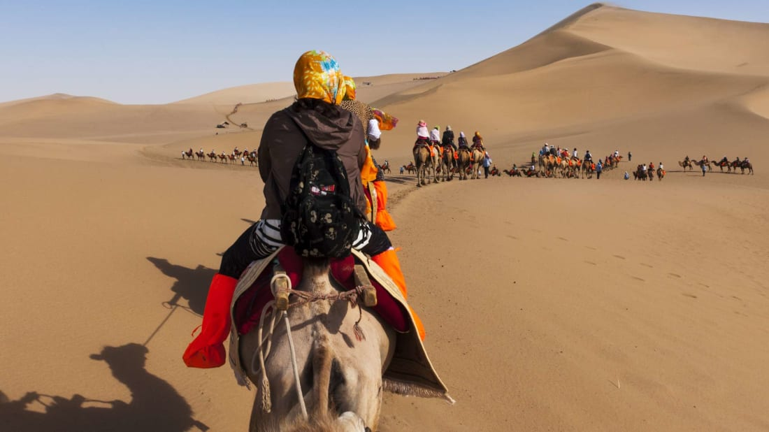 Tourists on a camel caravan explore he dunes around the city of Dunhuang, along the ancient Silk Road.