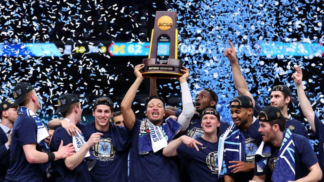 A euphoric Villanova men's basketball team brandishes the championship trophy after defeating the Michigan Wolverines in 2018's NCAA tournament.