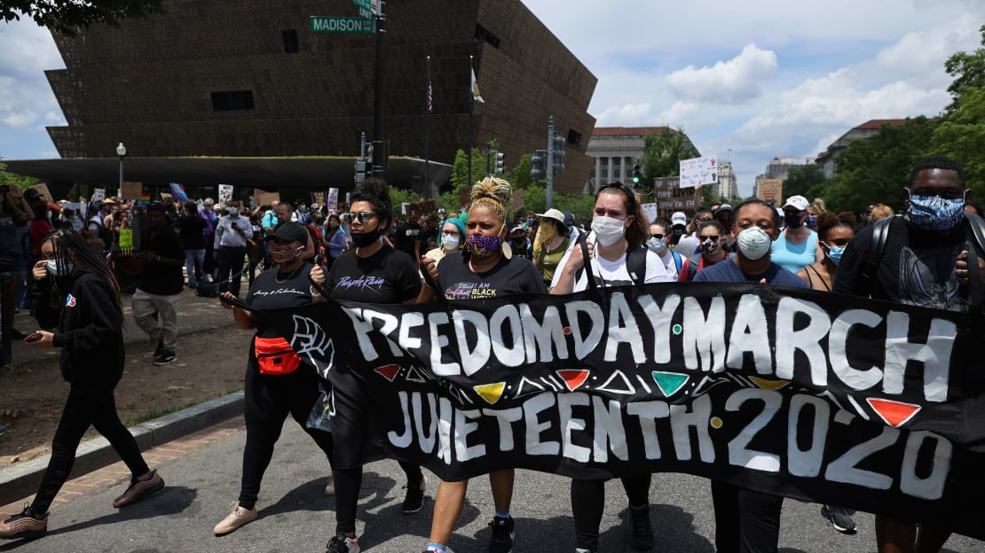 People walk by the National Museum of African American History and Culture during a 2020 Juneteenth march in Washington, D.C.