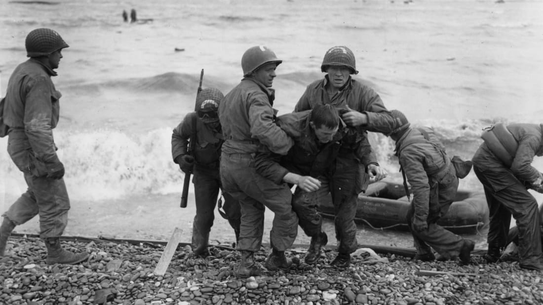 American troops helping their injured friends from a dinghy after the landing ship they were on was hit by enemy fire during the Allied invasion of France on D-Day