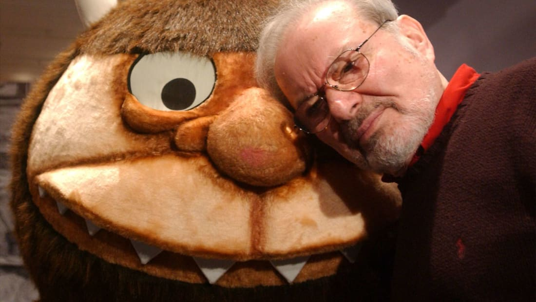 """author and illustrator Maurice Sendak standing with a character from his book """"Where the Wild Things Are"""" in 2002."""