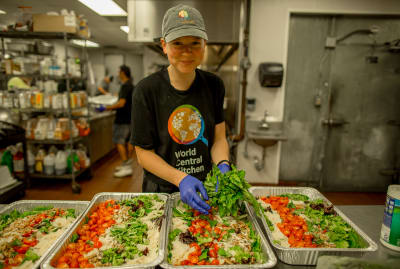 A volunteer for World Central Kitchen prepares hurricane relief meals.