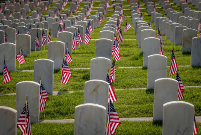 Military grave markers decorated with American flags for Memorial Day.