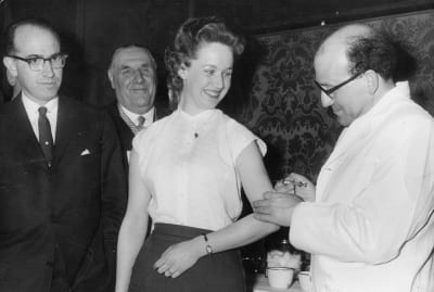 American doctor and epidemiologist Jonas Salk, who developed the first vaccine against poliomyelitis, looks on as a colleague gives the injection to a woman.