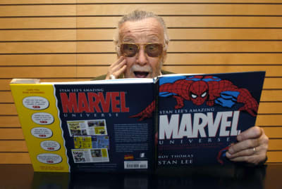 Comic book legend Stan Lee signs copies of his work.