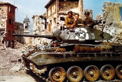 U.S. soldiers in an M24 Chaffee light tank driving through Bologna, Italy, in 1945.